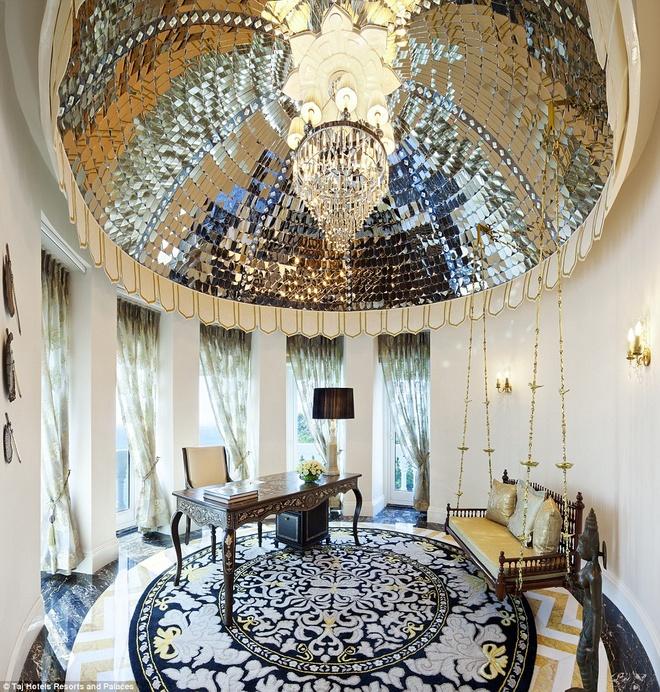 Nơi làm việc trong phòng Rajput Suite có sự kết hợp hài hòa giữa các vật dụng trang trí như chiếc bàn có họa tiết tỉ mỉ và ghế dài gắn xích đu bên dưới đèn chùm khổng lồ.