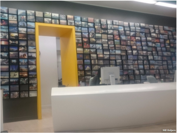 Bức tường đằng sau bàn lễ tân treo rất nhiều ảnh từ các chuyến du lịch của nhân viên công ty. Với chế độ phụ cấp du lịch từ 8.515 USD đến 14.192 USD, nhân viên của Expedia có cơ hội được đến rất nhiều nơi và có những trải nghiệm thú vị.