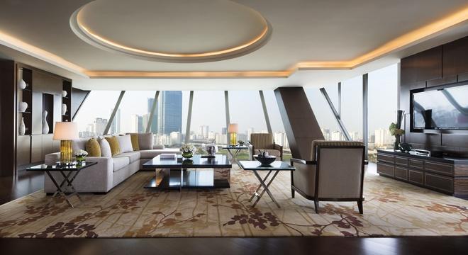 Căn phòng được thiết kế gồm 8 phòng riêng biệt. Trên hình là Phòng khách là phòng có diện tích lớn nhất. Nội thất trong phòng tổng thống mang phong cách trầm nhưng vẫn toát lên vẻ sang trọng và hiện đại nhờ sự kết hợp giữa đồ gỗ và thảm màu be, salon ghi sáng.