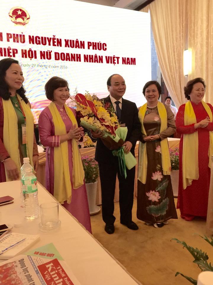 Thứ trưởng Bộ Công Thương Hồ Thị Kim Thoa, Chủ tịch Hiệp hội Nữ doanh nhân VN tặng hoa cho Thủ tướng Nguyễn Xuân Phúc nhân buổi gặp mặt.