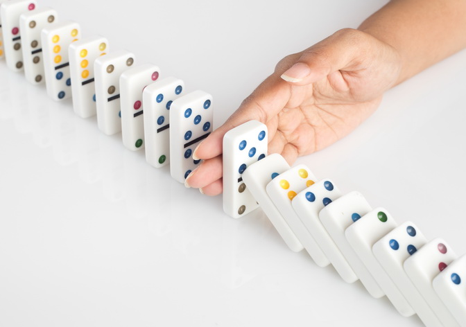 Human hand stopping a line of dominoes from falling. concept image for recovery plan and solution for cascading failures and problems. Dominoes are placed on a white table. High key image shot in studio.