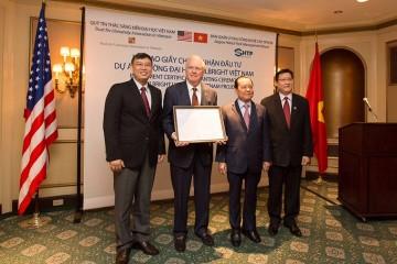 Ông Thomas Vallely, Giám đốc Chương trình Việt Nam tại Đại học Harvard cùng cộng sự nhận giấy chứng nhận đầu tư. Ảnh: TTXVN.