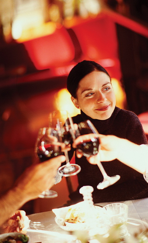 woman smiling while toasting red wine