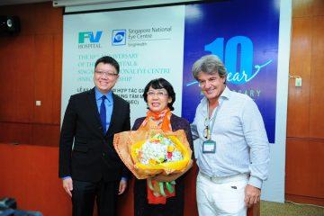 Bệnh nhân Nguyễn Thị Thanh Phương ở TPHCM, người được BS Edmund Wong điều trị thành công bệnh lý về võng mạc tại SNEC, nhận hoa chúc mừng từ BS Edmund Wong (trái) và BS Jean-Marcel Guillon, TGĐ bệnh viện FV.