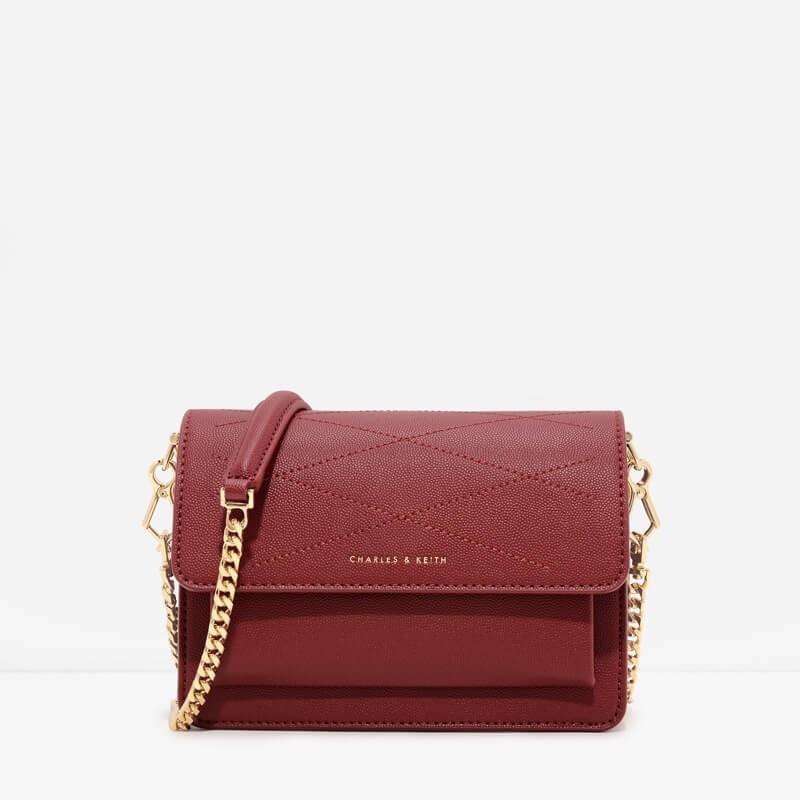 Thiết kế túi đeo chéo với đường thêu gân nổi, tạo điểm nhấn bên cạnh dây xích vàng đồng sang trọng.