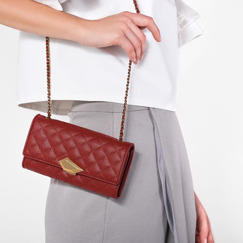 Mẫu ví chần bông màu đỏ mềm mại và vừa vặn, dễ dàng cầm tay hoặc đeo vai với thiết kế dây linh hoạt.
