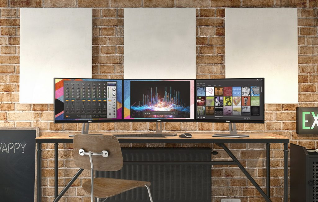 Commercial home office in industrial interior with brick background featuring three S2318H Monitors.