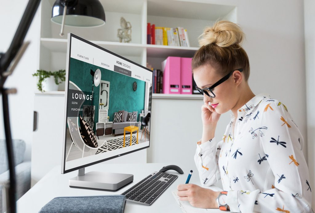 Young woman in casual clothes sitting at desk in home office with a Dell S2718D Monitor and KM717 Terra combo mouse and keyboard.