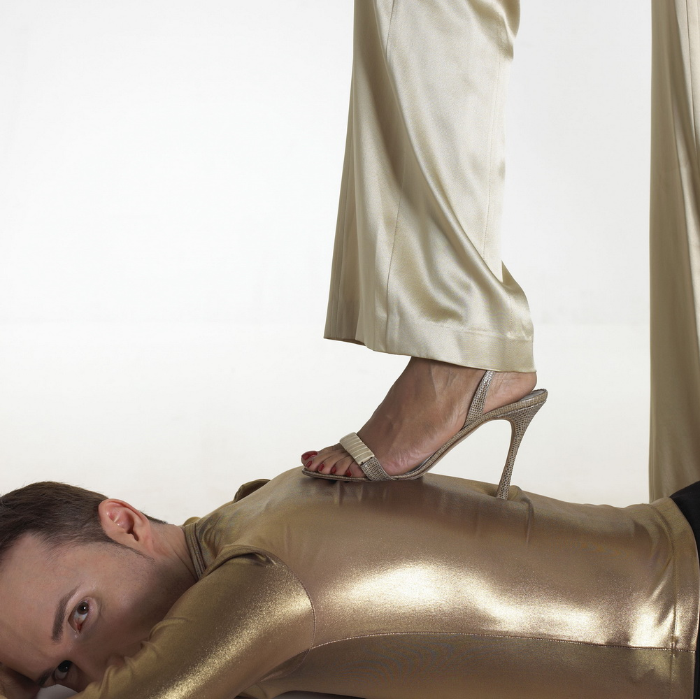 Woman stepping on man with stiletto heel