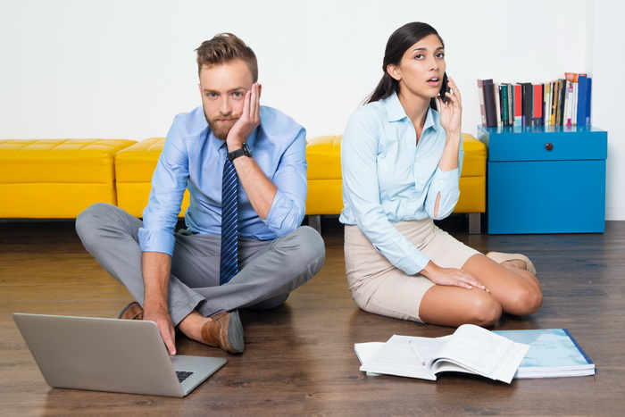 Unpleased businesswoman tired to listen to client. Depressed female manager using phone. Her business partner leaning head on hand and looking at camera. They working at home. They sitting on floor
