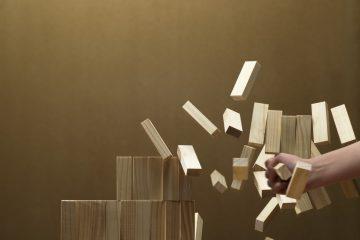 woman smashing a stack of wooden blocks