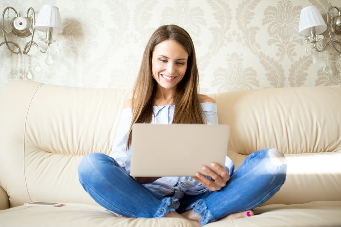 Portrait of cheerful young Caucasian woman wearing jeans sitting on sofa, networking on touchpad and smiling at home