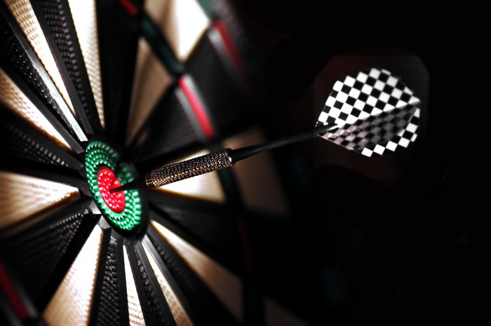 One arrow in the centre of a dart board. Shallow depth of field