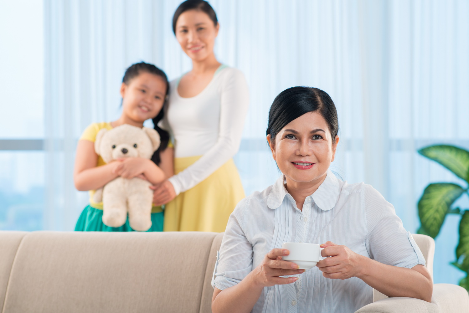Portrait of happy grandmother with cup of tea looking at camera wit hher daughter and granddaughter on background