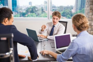 Serious young business leader explaining business issues to his team at meeting in office