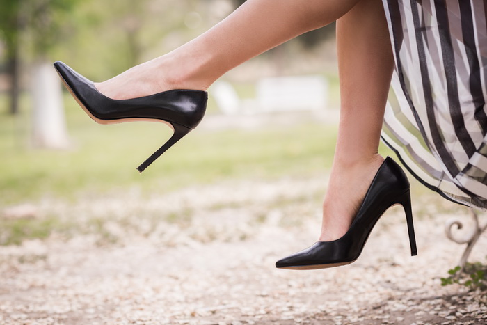 Black high heels on the feet of a young woman in a park