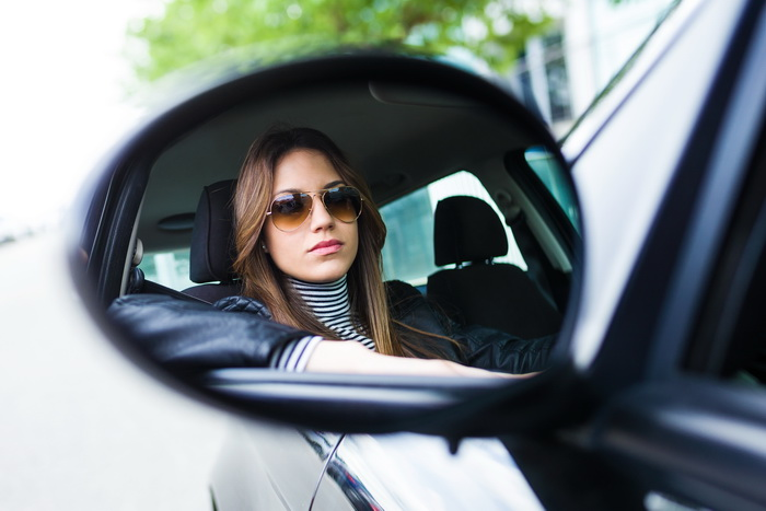 Portrait of beautiful young woman driving her car.