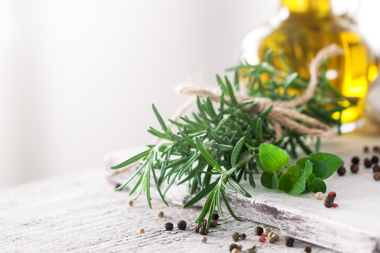 Healthy ingredients on a kitchen table - spaghetti, olive oil, spices and fresh italian herbs on a shiny background. Cooking, home cooking or healthy life concept, horizontal