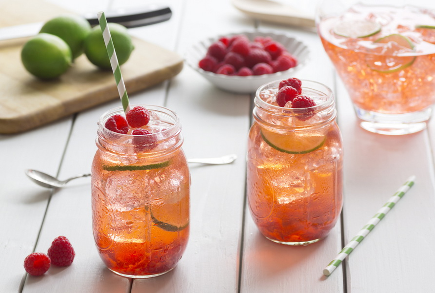 Raspberry lime iced tea in two glasses with straws. Ingredients for making tea are on the table in the background.