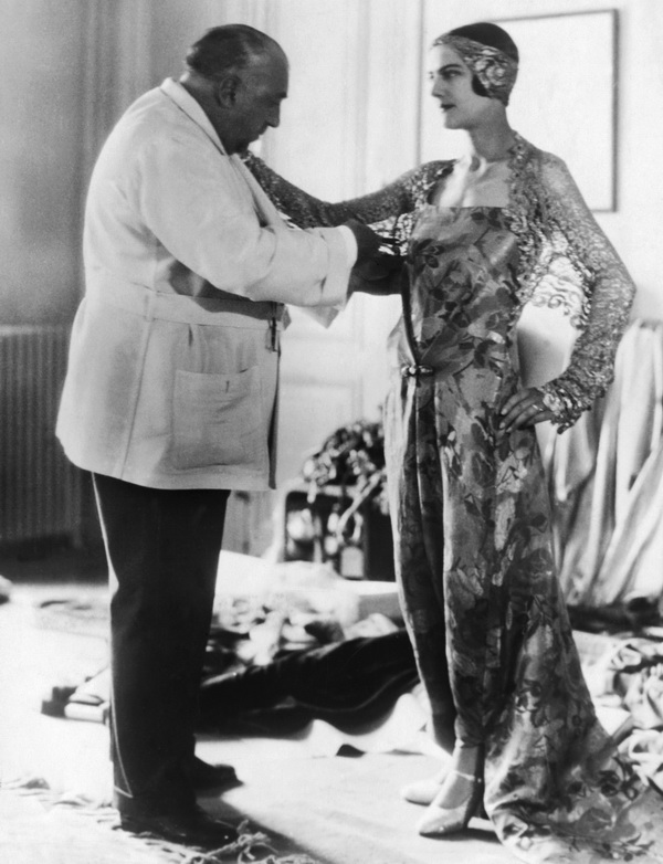 ca. 1930 --- Original caption: The internationally known figure, Paul Poiret, Parisian fashionmaker, whose skill in assembling a well-fashioned gown or dress has amazed thousands of American women during his tour of the United States, is shown fitting a woman with one of his creations. --- Image by © Underwood & Underwood/Corbis